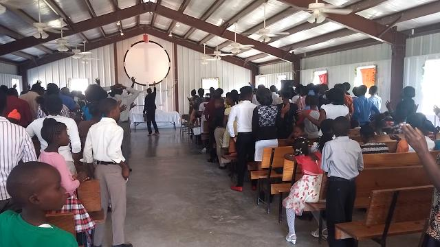 Frantzy Jwluc leads the congregation in a song during Sunday service in Onaville, Haiti.