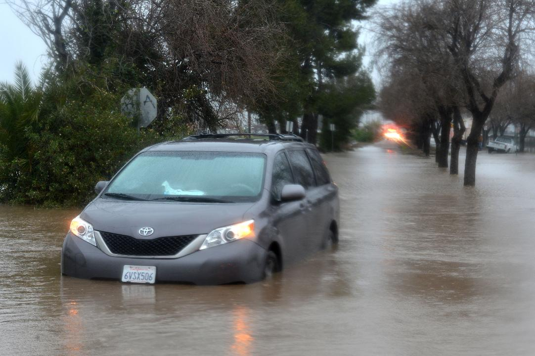Zachary Belanger and his father Cory Belanger are caught in floodwaters surging over Pleasant Valley Road on Sunday in Camarillo.
