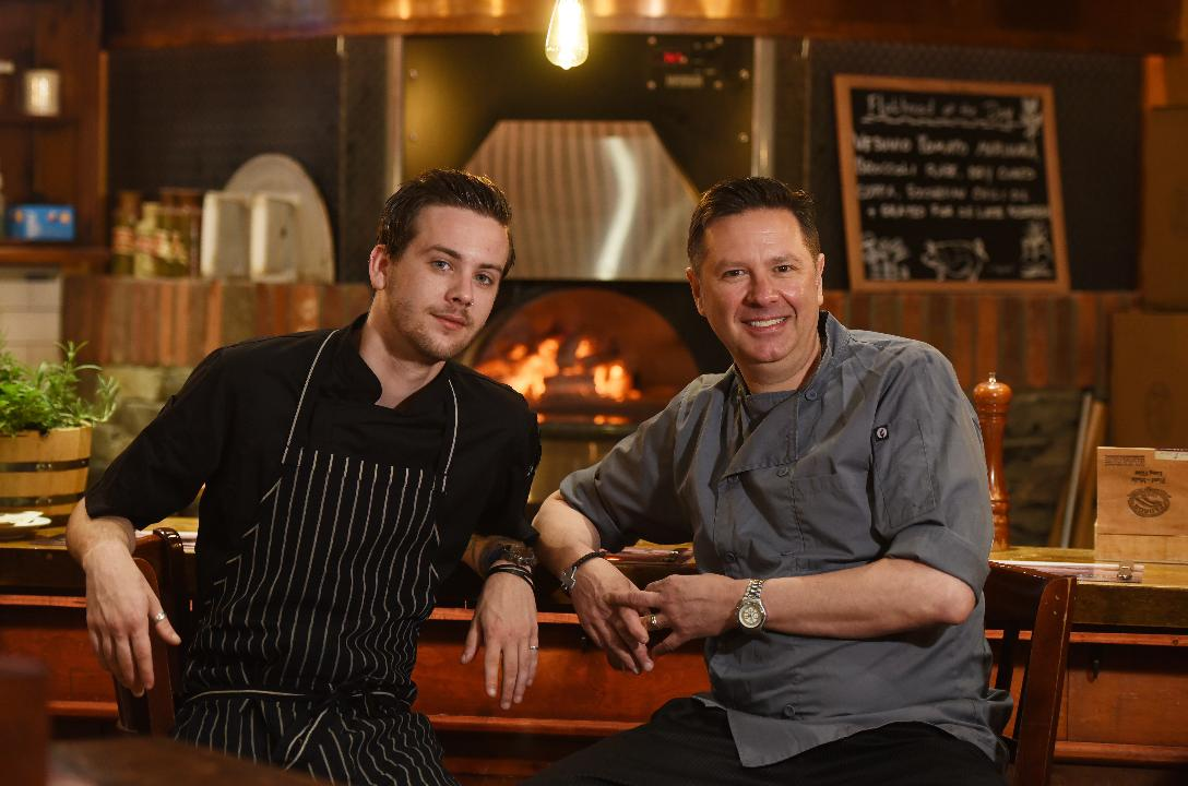 Exec. Chef Paul Bazzini works with his son Andrew (Sous Chef) behind the counter at Hearth & Tap Co. in Montvale.