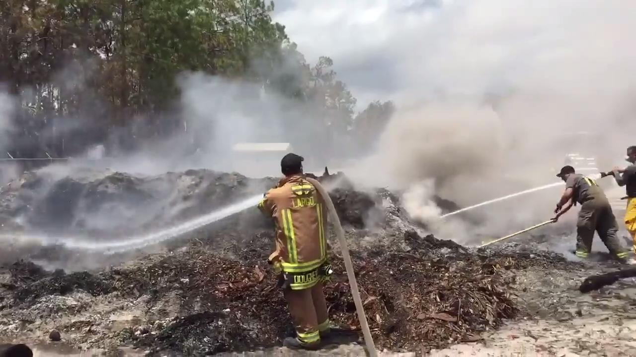 Firefighters put out a smoldering mulch fire at a landscaping business