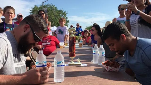 Kris Rollyson of Palm Bay (left) and Carlos Vargas of Savannah, Georgia go head-to-head Saturday, March 26, 2017, during the bacon speed-eating contest at the 2017 Vero Beach Bacon Fest.