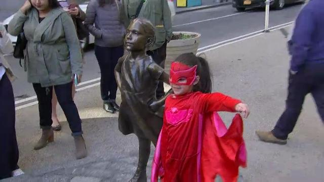"A statue of a young girl with a look of resolve was placed in front of Wall Street's famous charging bull in time for International Women's Day. ""Fearless Girl"" is intended to highlight efforts to get more women on corporate boards. (March 8)"
